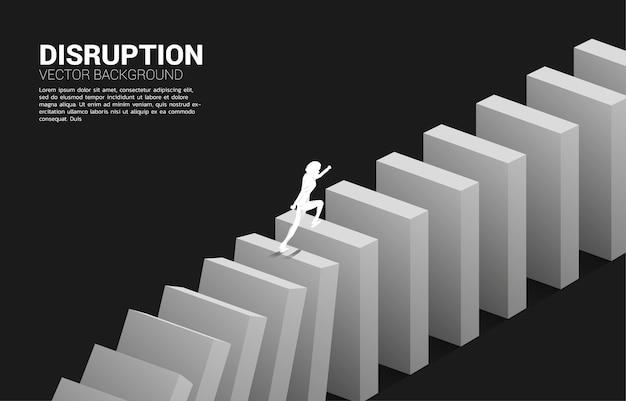 Przetrwać zakłócenia w biznesie. sylwetka biznesmena z upadkiem domina. koncepcja zakłócenia branży biznesowej