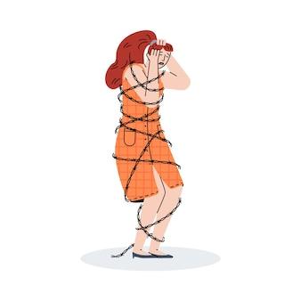 Przygnębiona młoda kobieta stoi zaplątana drutem kolczastym