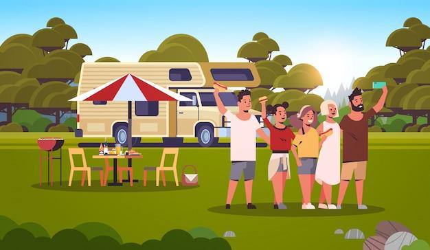 Przyjaciele robią selfie zdjęcie stojąc przy przyczepie na zewnątrz szczęśliwi mężczyźni kobiety grupa zabawy letni piknik grill party weekend koncepcja krajobraz tło płaskie pełnej długości poziome