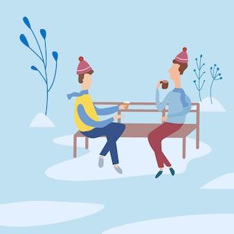 Przyjaciele rozmawiają w parku na ławce i piją kawę