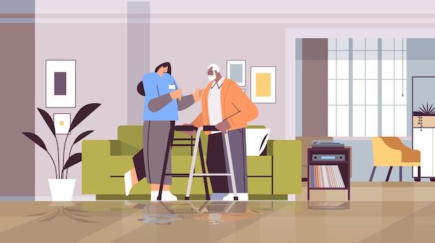 Przyjazna pielęgniarka lub wolontariusz wspierający afroamerykańskiego starszego mężczyznę z chodzikami usługi opieki domowej opieka zdrowotna i koncepcja wsparcia społecznego pozioma pełna długość