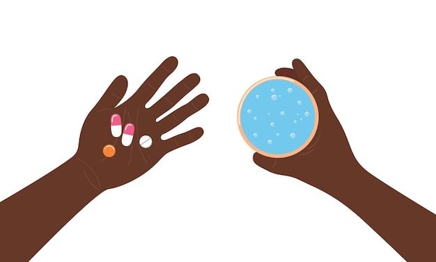 Przyjmowanie pigułek lekarstwa w widoku dłoni z góry ręce osoby z afryki, trzymającej tabletki i wodę