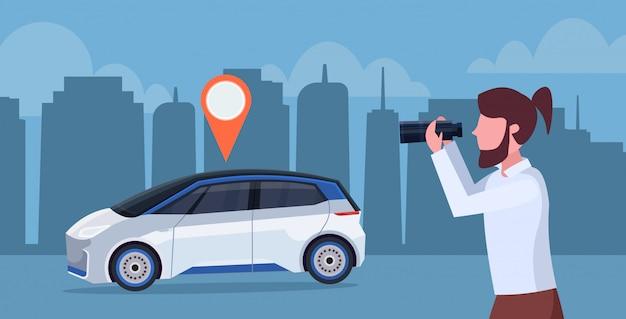 Przypadkowy mężczyzna patrzeje przez lornetek szuka samochód z lokaci szpilki czynszu wynajem samochodu pojęcia transportu carsharing usługa nocy pejzażu miejskiego tła horyzontalnym portretem