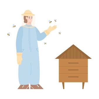 Pszczelarz w pasiece w kombinezonie ochronnym i kapeluszu stoi w pobliżu ula i latających pszczół