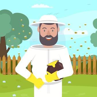 Pszczelarz w stroju ochronnym z miodem w ręku