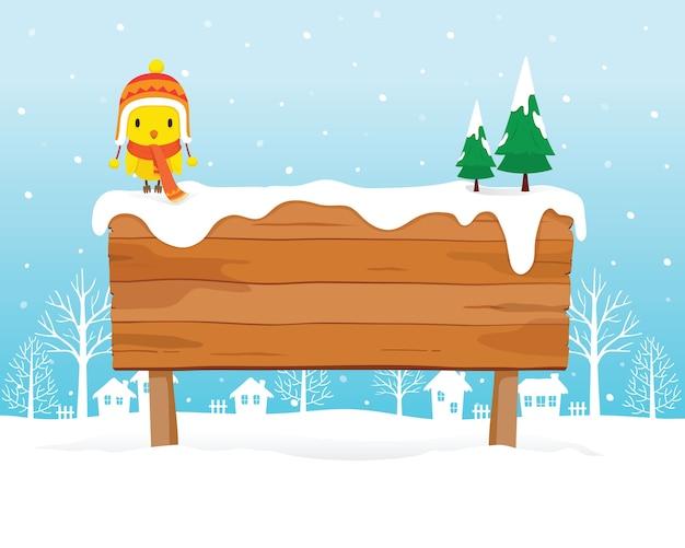 Ptak noszenie czapki zimowej i szalik siedzący na drewnianej tablicy na stosie śniegu, padający śnieg, sezon zimowy