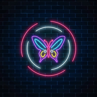 Purpurowy batterfly rozjarzony neonowy znak w round ramach na ciemnym ściana z cegieł tle. wiosna ulotki godło w okręgu.