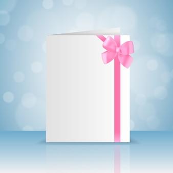 Pusta biała kartka z pozdrowieniami z romantyczną różową kokardką i wstążką z płaskim bokeh