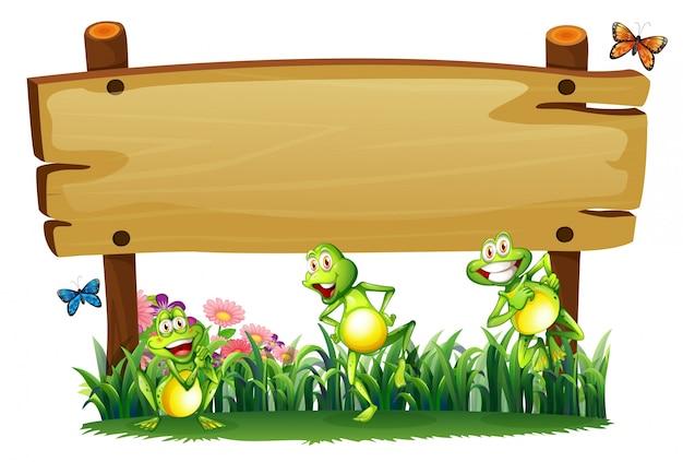 Pusta drewniana deska w ogrodzie z figlarnymi żabami