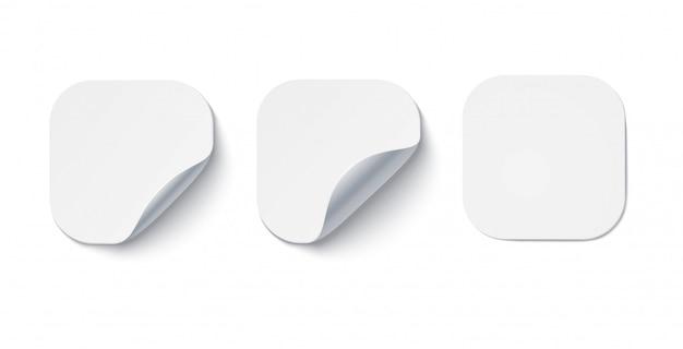 Puste białe naklejki samoprzylepne z zawiniętymi rogami na notatki. układy etykiet, metki z cenami.