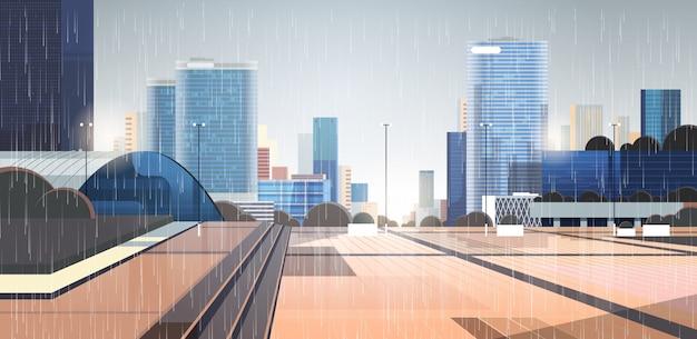 Puste krople deszczu w centrum miasta spadają na ulicę miasta bez ludzi i samochodów w deszczowy letni dzień