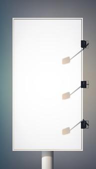 Puste pionowe billboard reklamowy na kolumnie z reflektorami i metalową ramą na białym tle