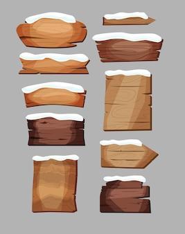 Puste szyldy lub drewniane deski o różnych kolorach i fakturach pokryte śniegiem.