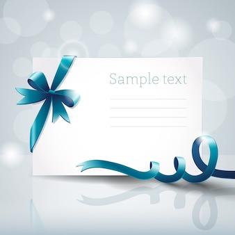 Pusty biały karton z pozdrowieniami z kokardą niebieską wstążką