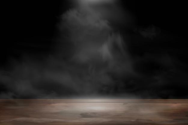Pusty drewniany stół z dymem unosi się na ciemnym tle. stół ze starego drewna z reflektorem i dymem w pokoju studio na prezentowany produkt.
