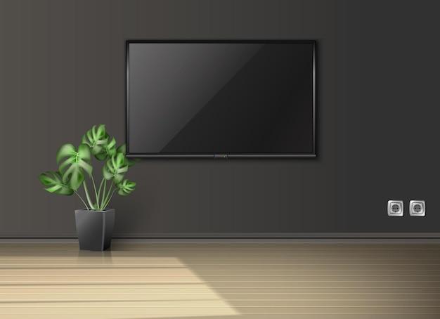 Pusty salon z ekranem na ścianie i rośliną w czarnej donicy z promieniami słońca wpadającymi przez okno.