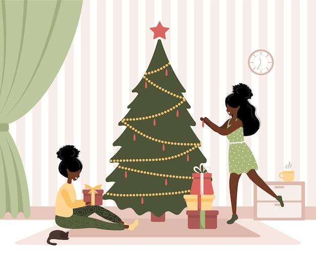Radosne afrykańskie kobiety ozdabiają choinkę. szczęśliwa para podczas przygotowań do świąt bożego narodzenia.