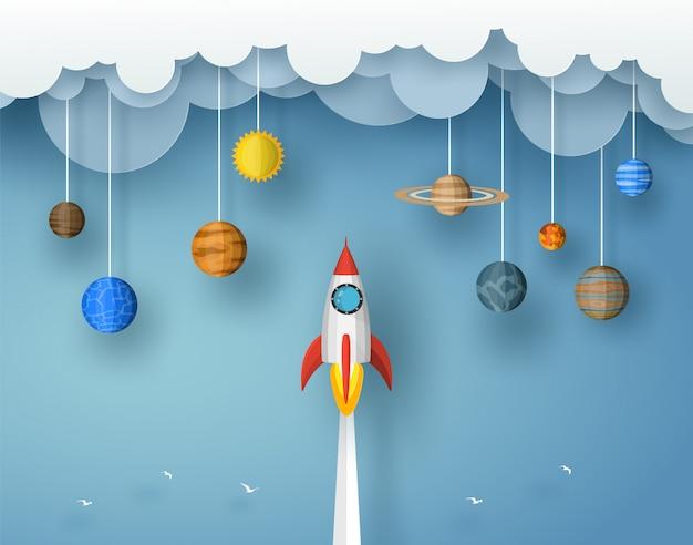 Rakieta wystrzelona do chmury z planetą origami i słońcem. wektor wzór w stylu cięcia papieru