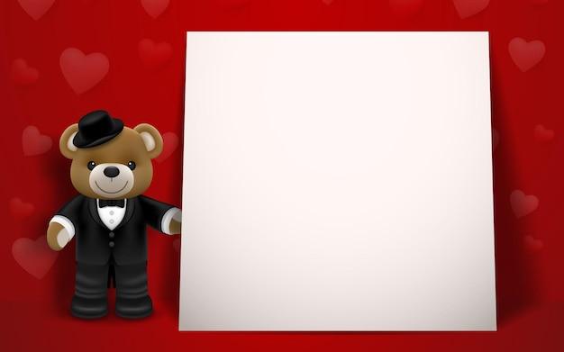 Realistyczna mała słodka uśmiechnięta lalka niedźwiedzia ubrana w smoking, trzymająca pudełko i stojąca obok białej ramki na czerwonym tle. koncepcja walentynki i miłość