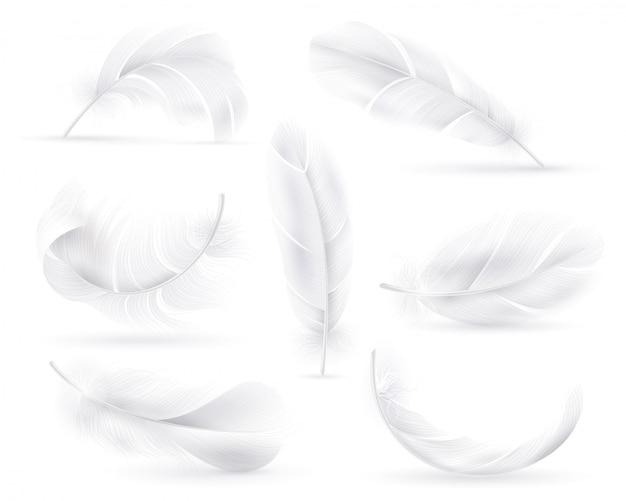 Realistyczne białe pióra. spadające puszyste, kręcone pióra ptaka lub anielskie skrzydła. latające, pływające ozdobne pióro wektor niewinność element dekoracji kształtuje pióropusz na białym tle zestaw