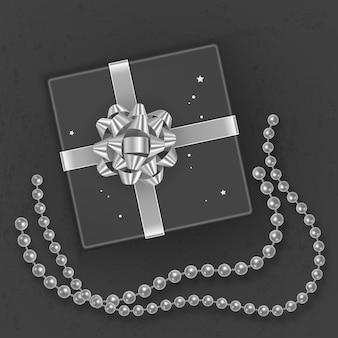 Realistyczne czarne pudełko upominkowe ozdobione srebrną kokardką, widok z góry.