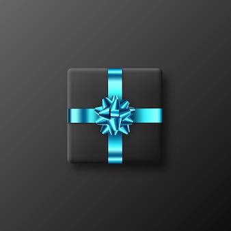 Realistyczne czarne pudełko z błyszczącą niebieską kokardką i wstążką. element dekoracyjny na wakacje. ilustracja wektorowa.