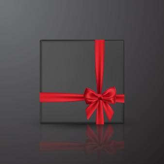 Realistyczne czarne pudełko z czerwoną kokardką i wstążką. element do dekoracji, prezenty, pozdrowienia, święta.