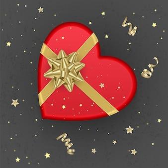 Realistyczne czerwone pudełko upominkowe w kształcie serca ozdobione złotą kokardką, widok z góry.