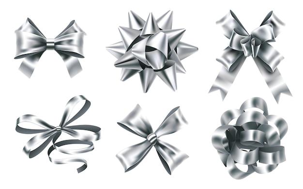 Realistyczne kokardki ze srebrnej folii. ozdobna kokardka, metalowa wstążka uprzejmości i znaki kokardki na prezenty świąteczne.