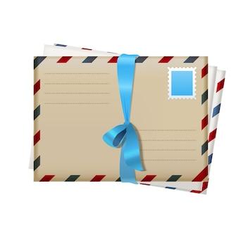 Realistyczne koperty pocztowe z niebieską wstążką i znaczkiem pocztowym w stylu vintage