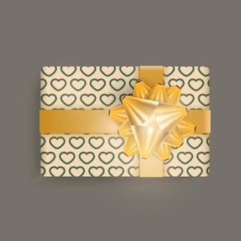 Realistyczne pudełko upominkowe w kolorze szampana ze wzorem w serca, złotymi wstążkami i kokardką.