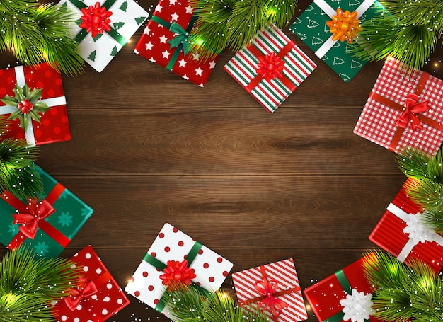 Realistyczne tło boże narodzenie z kolorowe pudełka i gałęzie jodły na drewnianym stole