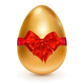 Realistyczne złote jajko wielkanocne przewiązane czerwoną wstążką z dużą czerwoną kokardą.