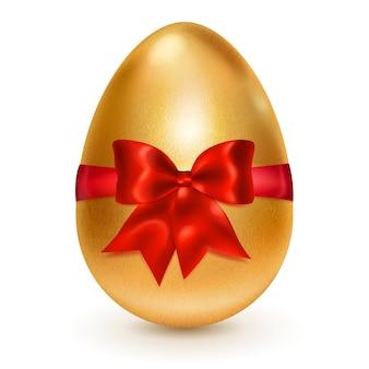 Realistyczne złote jajko wielkanocne przewiązane czerwoną wstążką z dużą czerwoną kokardką