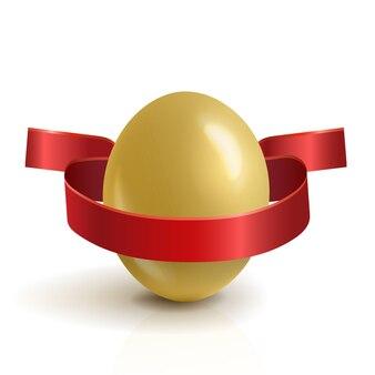 Realistyczne, złote jajko wielkanocne z czerwoną wstążką.
