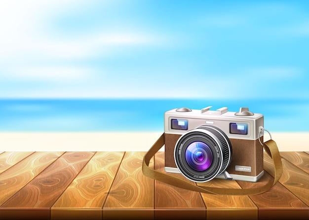 Realistyczny aparat fotograficzny retro vintage na drewnianej podłodze na piasku w tle plaży wybrzeża