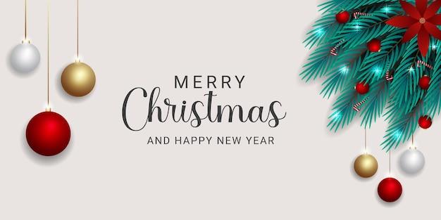 Realistyczny świąteczny sztandar z zielonymi gałązkami, czerwone kwiatowe cukierki i bożonarodzeniowa kula