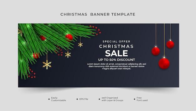 Realistyczny szablon transparentu świątecznej wyprzedaży z zielonym liściem i czerwoną kulką