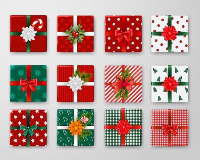 Realistyczny zestaw owiniętych świątecznych prezentowych pudeł z kolorowymi wstążkami i kokardkami na białym tle
