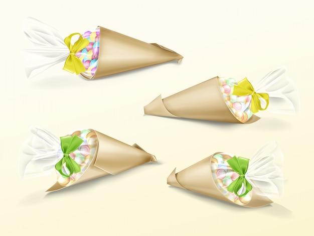Realistyczny zestaw papierowych toreb stożkowych z kolorowymi słodyczami dragee i żółtą i zieloną taśmą jedwabną