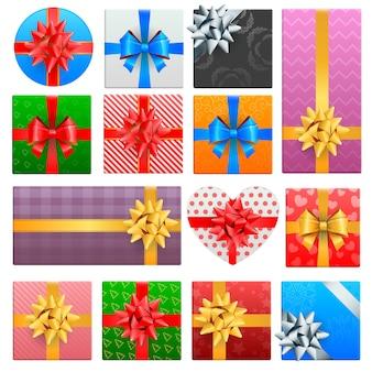 Realistyczny zestaw zapakowany w pudełka na prezenty świąteczne z kokardkami z kolorowych wstążek