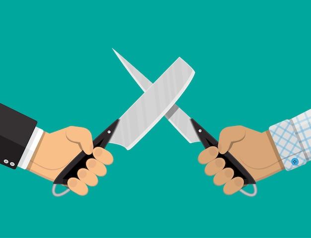 Ręce biznesmenów z nożami.