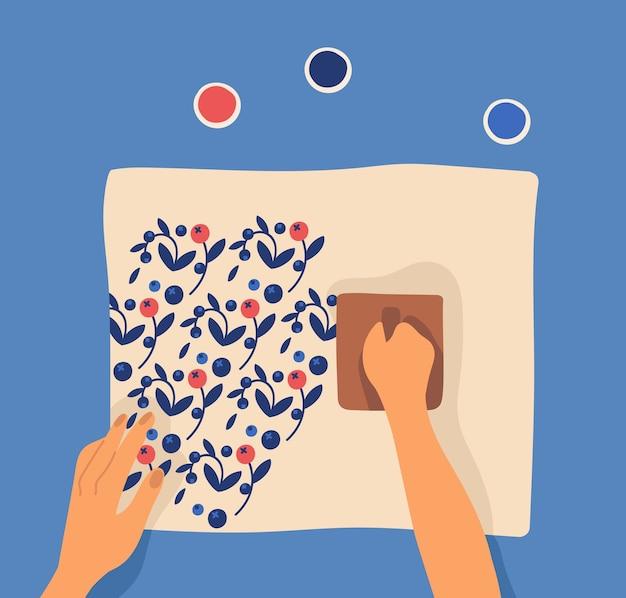 Ręce drukują wzór na tkaninie za pomocą klocków i farby