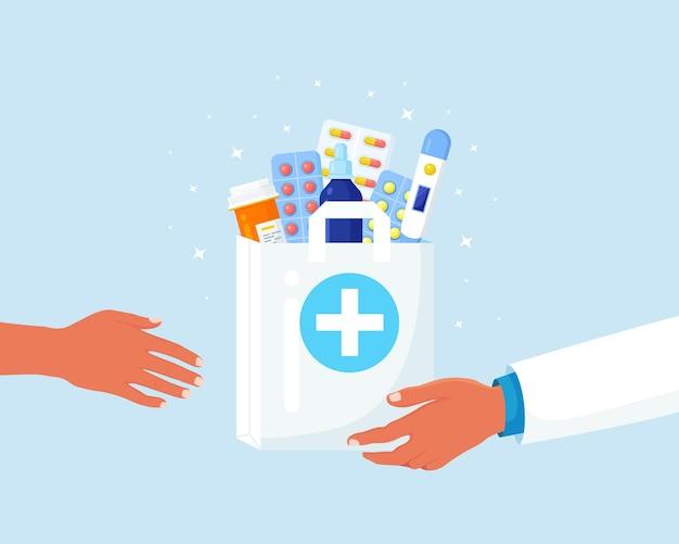 Ręce kurierskie w jednorazowych rękawiczkach trzymają papierową torbę z butelką tabletek, lekarstwami, lekami, termometrem w środku. farmaceuta udziela zakupu klientowi. usługa apteki z dostawą do domu