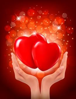 Ręce, trzymając dwa czerwone serca
