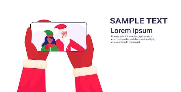 Ręce trzymając smartfon święty mikołaj z afroamerykańską pomocniczką elf na ekranie koncepcja uroczystości świątecznych online aplikacja mobilna portret kopia przestrzeń ilustracja