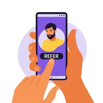 Ręce trzymając smartfon z profilem w mediach społecznościowych lub kontem użytkownika. poleć znajomemu, postępując zgodnie z koncepcją dodania.