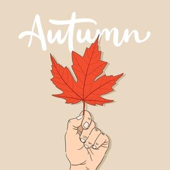 Ręcznie rysowane ręka trzyma jesień liść klonu ilustracja