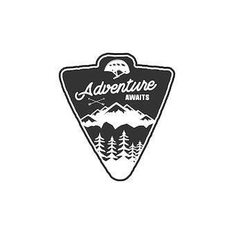 Ręcznie rysowane rocznika odznaka kempingowa i etykieta piesze wycieczki z górami, lasem, wspinać się na kask i projekt typografii. tekst cytatu - przygoda czeka. naszywka w starym stylu. szablon wektor rustykalny stempel.