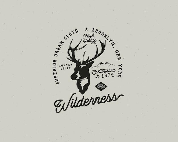 Ręcznie rysowane vintage odznaka camping i wędrówki etykiety z elementami turystyki pieszej i typografii. w zestawie głowa jelenia, góry i tekst cytatu - dzicz. naszywka w starym stylu. szablon łaty rustykalnej